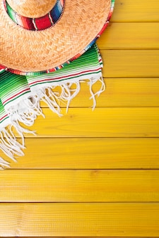 Mexican sombrero and traditional serape blanket laid on a yellow painted pine wood floor