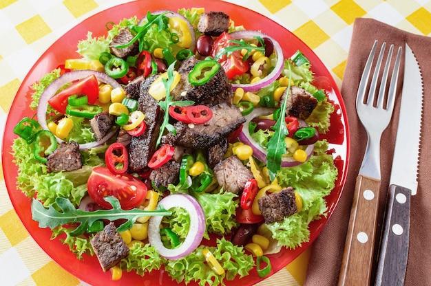 Мексиканский острый салат из говядины на тарелке. мясо говядины на гриле с вкусным выбором овощей.