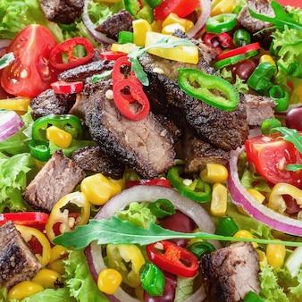 접시에 멕시코 매운 쇠고기 샐러드입니다. 엄선된 야채와 함께 구운 쇠고기 고기.