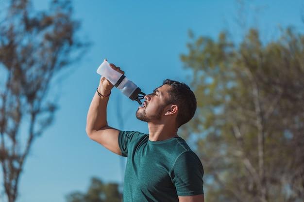 Мексиканский спортивный мужчина пьет воду
