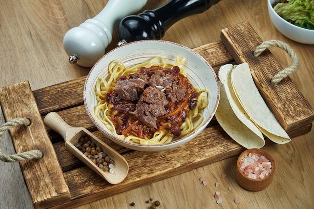 Лапша в мексиканском стиле - кукурузная паста с чили кон карне, тушеной говядиной и тако в керамической тарелке. современная мексиканская кухня. еда плоская планировка