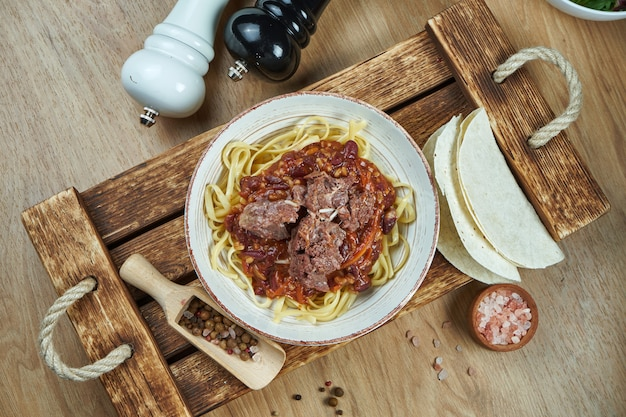 Mexican style noodles - corn paste with chili con carne, stewed beef and tacos in a ceramic plate. modern mexican cuisine. food flat lay