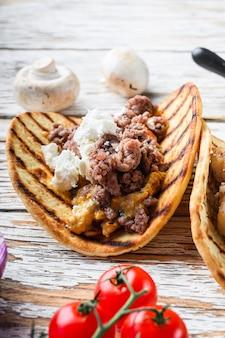 牛肉と食材を使ったメキシコのタコス、白い質感の木製の表面テーブル、側面図