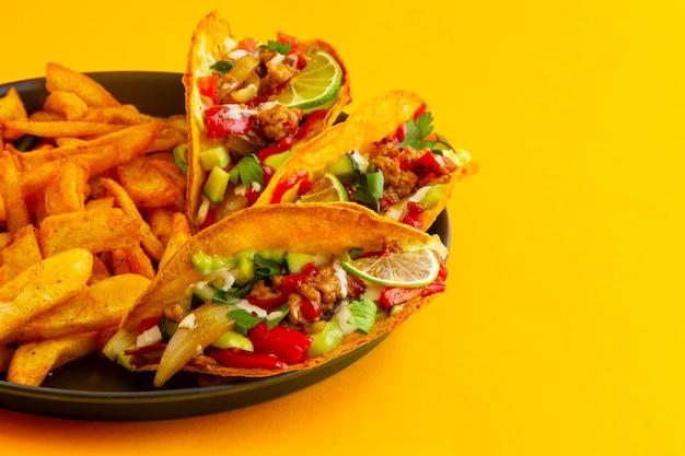 Мексиканские тако с французским картофелем в черном паштетах на желтом фоне