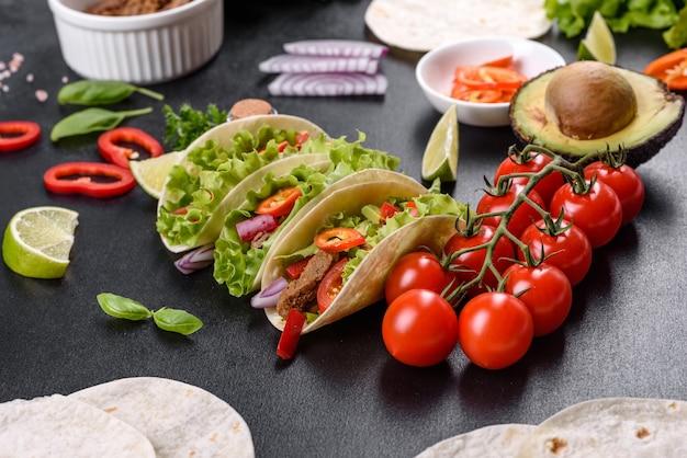 牛肉、トマト、アボカド、タマネギ、サルサソースのメキシコのタコス
