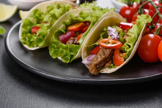 Mexican tacos with beef, tomatoes, avocado, onion and salsa sauce