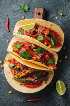 Mexican tacos with beef, vegetables and salsa.