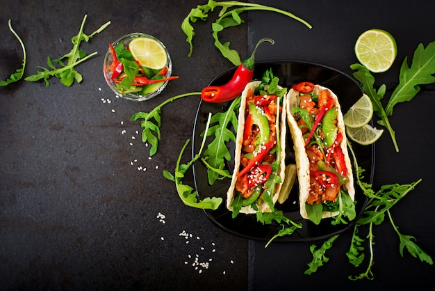 Mexican tacos with chicken fillet in tomato sauce and salsa of paprika and arugula. flat lay. top view