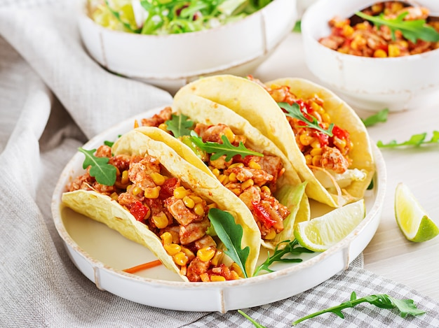Mexican tacos with chicken meat, corn and tomato sauce