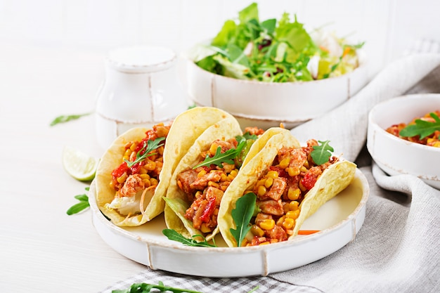 Mexican tacos with chicken meat, corn and tomato sauce.
