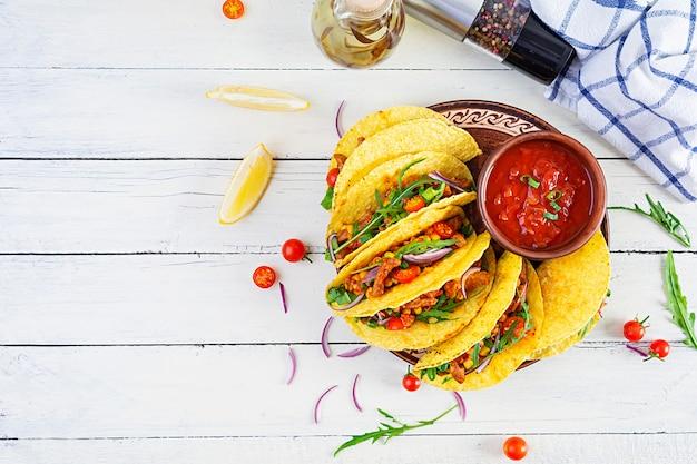 木製のテーブルにコーントルティーヤと肉を添えたメキシコのタコス。上面図
