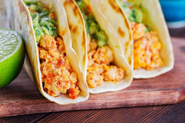 Mexican tacos with fried minced chicken and guacamole sauce on a wooden boards. tacos, guacamole and lime on wooden background. mexican cuisine