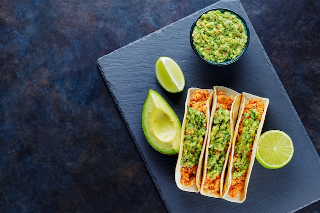Mexican tacos with fried minced meat. tacos with chicken and guacamole on a dark background. mexican traditional cuisine. copy space. top view