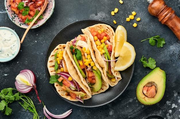 Мексиканские тако с жареной курицей, авокадо, кукурузными зернами, помидорами, луком, кинзой и сальсой за черным каменным столом. традиционная мексиканская и латиноамериканская уличная еда. вид сверху.