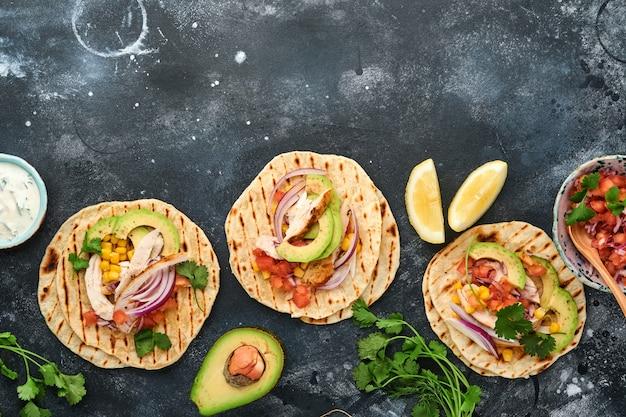 검은 돌 테이블에 구운 닭고기, 아보카도, 옥수수 커널, 토마토, 양파, 실란트로, 살사가 있는 멕시코 타코. 전통적인 멕시코 및 라틴 아메리카 길거리 음식. 평면도.