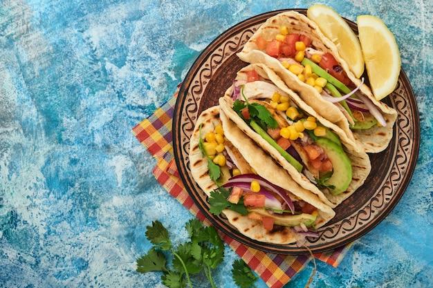 Мексиканские тако с жареной курицей, авокадо, кукурузными зернами, помидорами, луком, кинзой и сальсой за столом blue stone. традиционная мексиканская и латиноамериканская уличная еда. вид сверху.