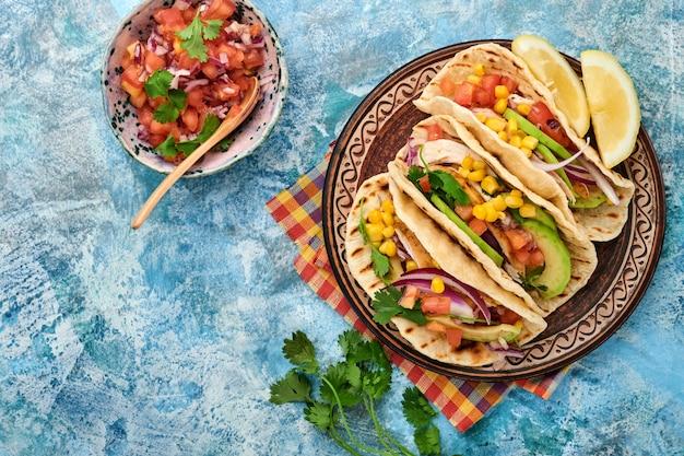 青い石のテーブルにグリルチキン、アボカド、トウモロコシの実、トマト、タマネギ、コリアンダー、サルサを添えたメキシコのタコス。伝統的なメキシコとラテンアメリカの屋台の食べ物。上面図。