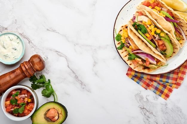 Мексиканские тако с жареной курицей, авокадо, кукурузными зернами, помидорами, луком, кинзой и сальсой за белым каменным столом. традиционная мексиканская и латиноамериканская уличная еда. вид сверху.