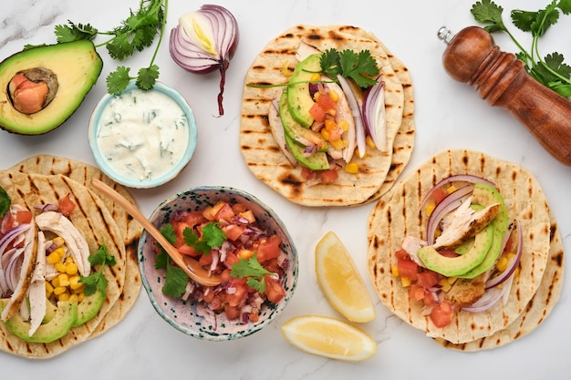 구운 닭고기, 아보카도, 옥수수 커널, 토마토, 양파, 실란트로, 살사가 하얀 돌 테이블에 있는 멕시코 타코. 전통적인 멕시코와 라틴 아메리카 길거리 음식. 평면도.