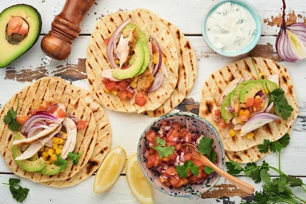 Мексиканские тако с жареной курицей, авокадо, кукурузными зернами, помидорами, луком, кинзой и сальсой на старом белом деревянном столе. традиционная мексиканская и латиноамериканская уличная еда. вид сверху.