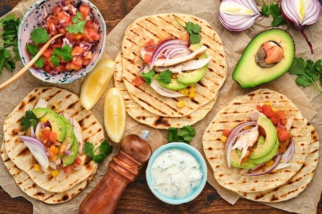 구운 닭고기, 아보카도, 옥수수 커널, 토마토, 양파, 실란트로, 살사 오래된 나무 테이블이 있는 멕시코 타코. 전통적인 멕시코 및 라틴 아메리카 길거리 음식. 평면도.
