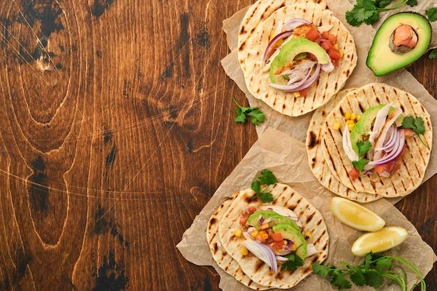 구운 닭고기, 아보카도, 옥수수 커널, 토마토, 양파, 실란트로, 살사 오래된 나무 테이블이 있는 멕시코 타코. 전통적인 멕시코와 라틴 아메리카 길거리 음식. 평면도.