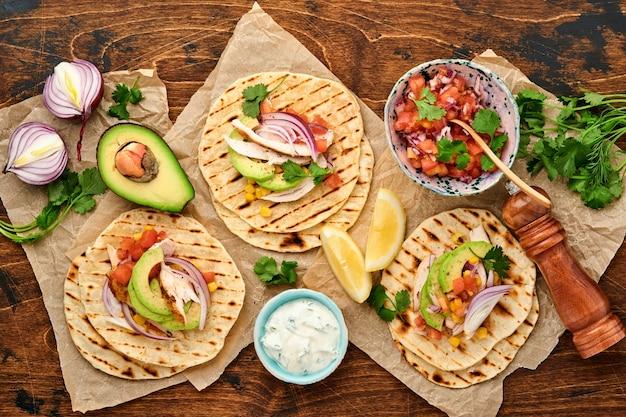 Мексиканские тако с жареной курицей, авокадо, кукурузными зернами, помидорами, луком, кинзой и сальсой на старом деревянном столе. традиционная мексиканская и латиноамериканская уличная еда. вид сверху.