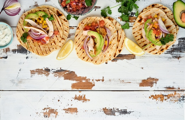 Mexican tacos with grilled chicken, avocado, corn kernels, tomato, onion, cilantro and salsa old white wooden table. traditional mexican and latin american street food. top view.