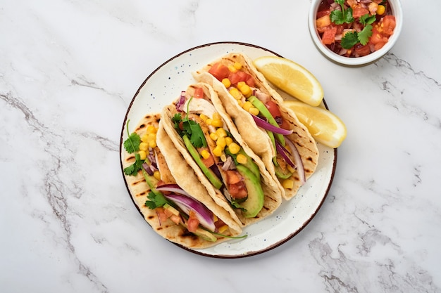 Mexican tacos with grilled chicken, avocado, corn kernels, tomato, onion, cilantro and salsa at white stone table. traditional mexican and latin american street food. top view.