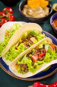 Мексиканские тако с мясом, фасолью, кукурузой, сальсой и овощами на тарелке. вид сверху. техасско-мексиканская кухня.