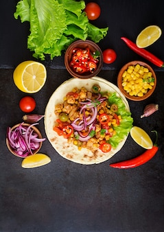 Mexican tacos with meat, corn and olives on dark background. top view