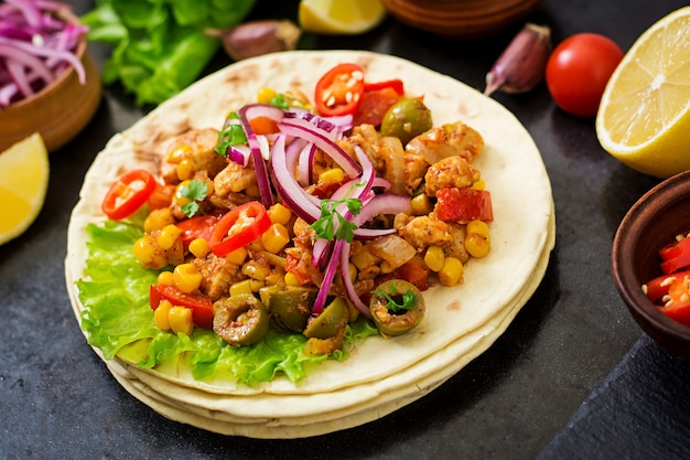 Mexican tacos with meat, corn and olives on dark background.