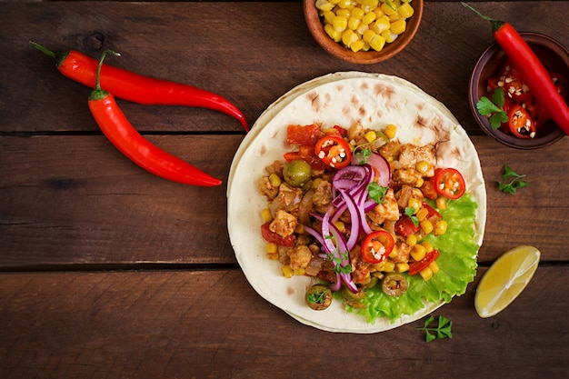 Mexican tacos with meat, corn and olives on wooden background. top view