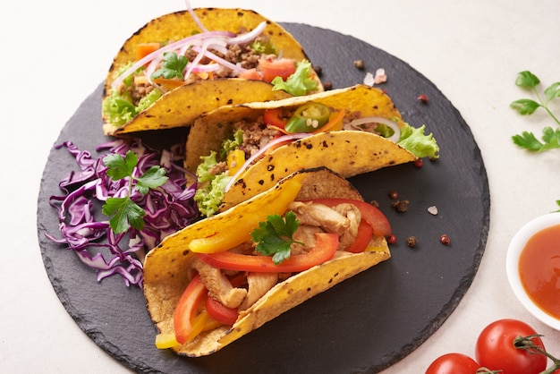 Mexican tacos with meat, pork carnitas street tacos in yellow corn tortilla with onion, cilantro and cabbage. red cabbage. top view. flat lay.
