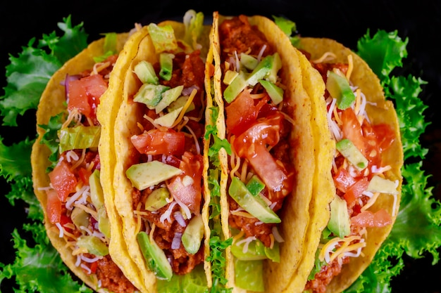 Mexican tacos with meat and vegetables on black plate on wooden background