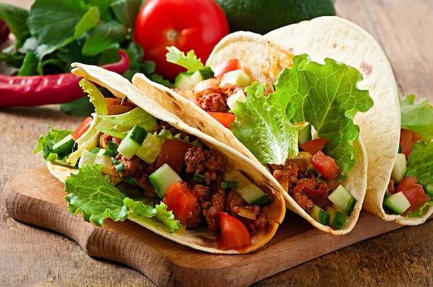 Mexican tacos with meat, vegetables and cheese