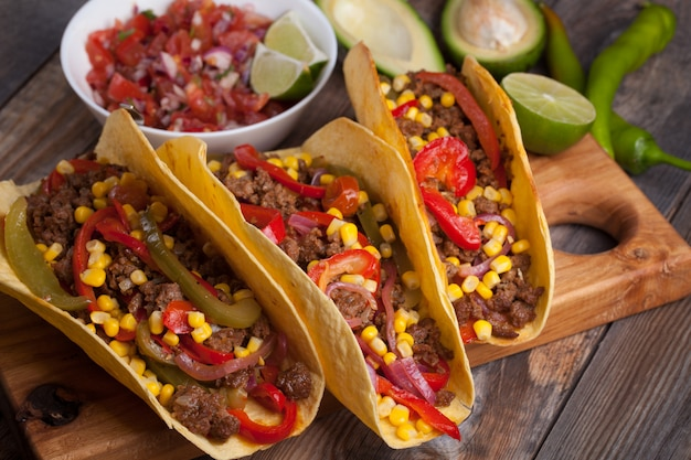 Mexican tacos with minced beef, vegetables and salsa.