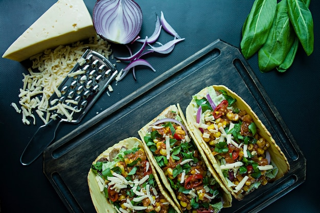 Mexican tacos with pork meat, cheese, corn, onions and herbs on a wooden board