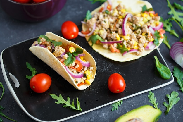 Mexican tacos with pork, vegetables and spices on a black stone plate on a dark background with ingredients for tacos