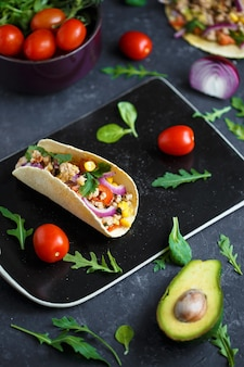 Mexican tacos with pork, vegetables, tomatoes, avocado and spices on a black stone plate on a dark background with ingredients for tacos