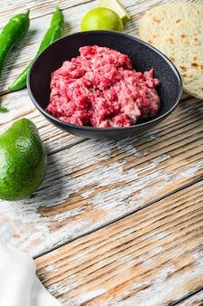 白い織り目加工の木製の背景の上に野菜とひき肉の食材を使ったメキシコのタコス、テキスト用のスペースのある側面図。