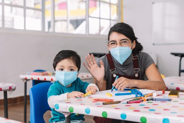 メキシコの教師とcovid-19検疫後の学校でマスクを持つ子供