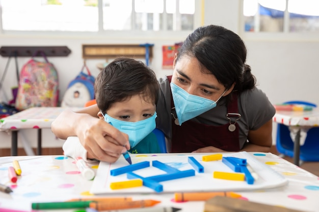 Mexican teacher and child with masks at school after covid-19 quarantine
