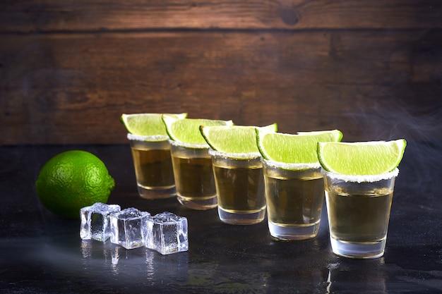Мексиканская текила золото в коротких очках с солью, ломтиками лайма и льда на деревянном столе. дым.
