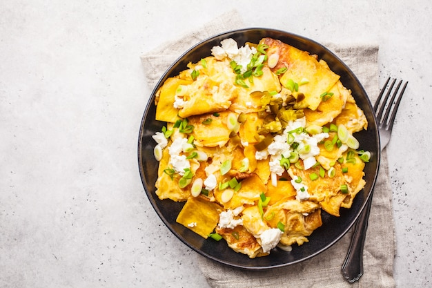 Mexican tortilla egg migas with feta and green onions in a black plate on white background, top view.