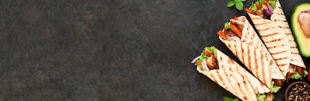 コンクリートの背景に鶏の胸肉と野菜のメキシコのトルティーヤグリルラップ