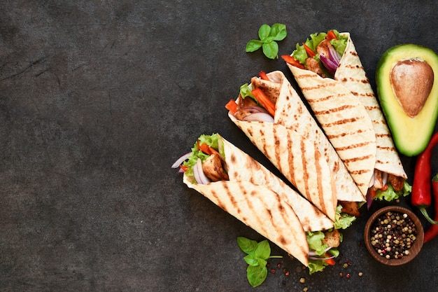 Mexican tortilla grilled wrap with chicken breast and vegetables on concrete background