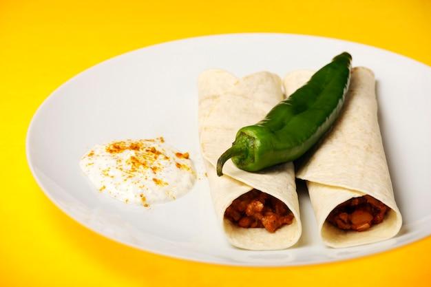 Мексиканская тортилья с говядиной на желтом фоне