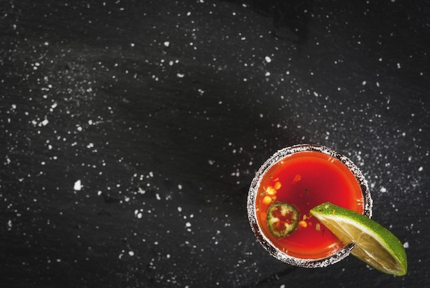 Mexican traditional alcohol drink. sangrita with tequila tomato juice hot spices chili and lime.analogous bloody mary. on black slate table