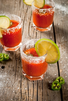 Mexican traditional alcohol drink. sangrita with tequila tomato juice hot spices chili and lime.analogous bloody mary. on rustic wooden table